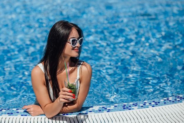 プールで入浴し、さわやかなカクテルを飲む美しい姿の若い美しい少女。