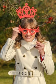 매력적인 미소와 갈색 머리를 가진 젊은 아름 다운 소녀는 안경 및 크라운 그의 손에 마스크를 보유하고있다.