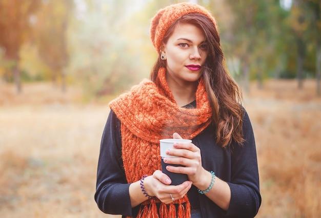 屋外の公園を散歩するためのコーヒー(お茶)と若い美しい少女。秋の天気。太陽光線がモデルを後ろから照らします。