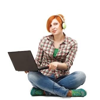 ヘッドフォンで音楽を聴いて楽しんでラップトップを持つ若い美しい女の子白で隔離