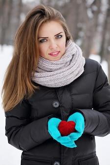 彼女の手に赤いハートを持つ若い美しい少女
