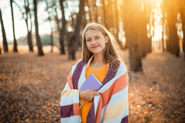 가을 공원에서 보라색 단편 소설책을 들고 있는 아름다운 소녀
