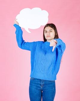 Молодая красивая девушка с белым пузырем для текста, показывая большой палец вниз.