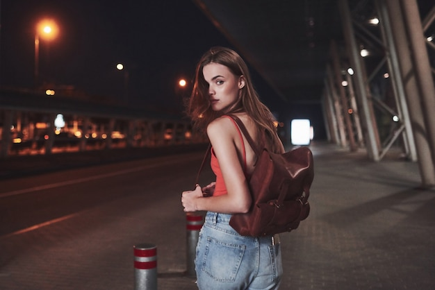 A young beautiful girl with a backpack behind her shoulders stands on the street near an airport
