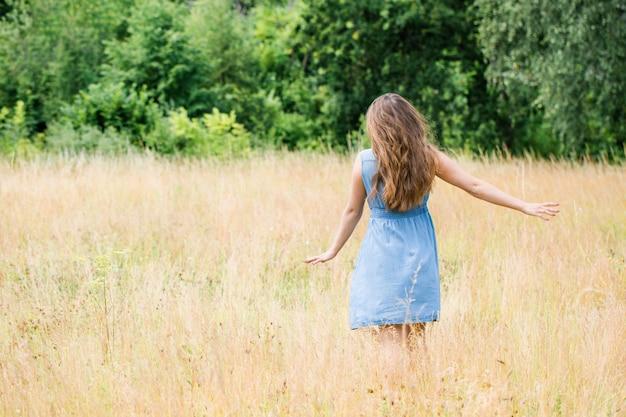 Молодая красивая девушка с красивыми длинными волосами в синем платье идет по полю