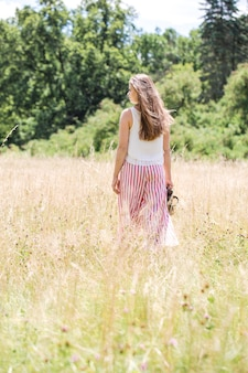 Молодая красивая девушка с красивыми длинными волосами в полосатых брюках гуляет по полю