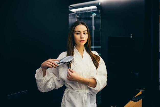 白衣を着た黒い髪の若い美しい少女は、お風呂の後に彼女の髪をとかします