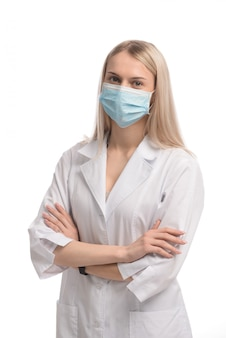 Молодая красивая девушка со светлыми волосами в медицинской маске на белом фоне