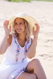 夏のドレスと帽子のブロンドの髪の少女は海岸の砂の上に座っています