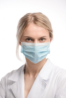 Young beautiful girl with blond hair in a medical mask on white background