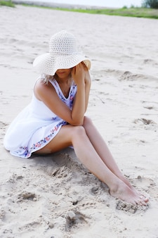 Young beautiful girl with blond hair in a summer dress and hat sits on the sand on the shore