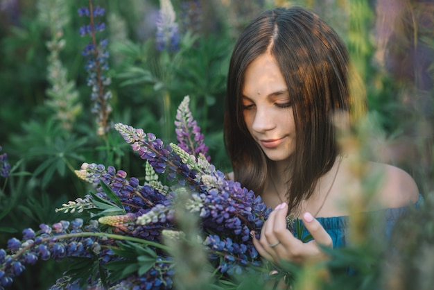 Young beautiful girl with a bouquet of purple lupins in a field at sunset. nature concept.