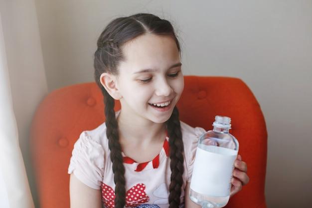 Молодая красивая девушка с косами с бутылкой воды.