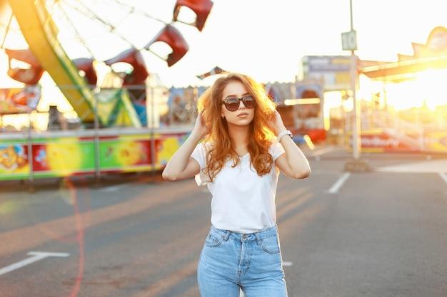 日没の夏の日に遊園地に立っている真っ赤な髪の少女