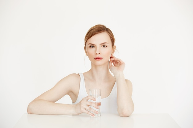 Young beautiful girl with clean fresh skin holding glass with water sitting at table . health and beauty lifestyle.