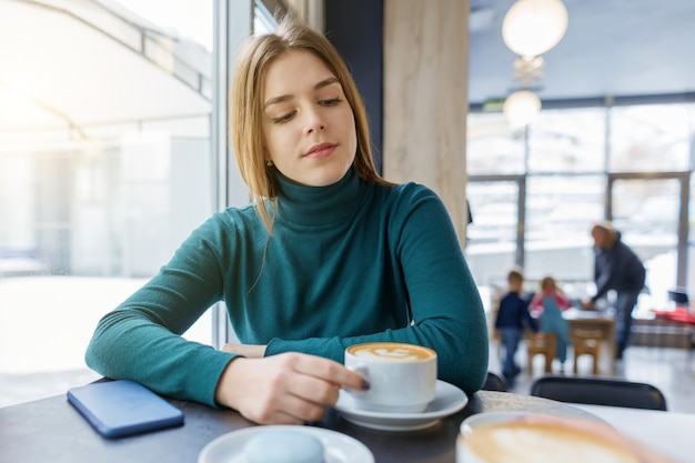 Young beautiful girl with cup of coffee