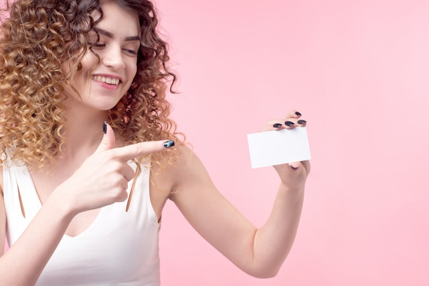 곱슬 머리를 가진 아름 다운 소녀는 그녀의 손에 카드를 보유 하 고 그것을 보여줍니다.