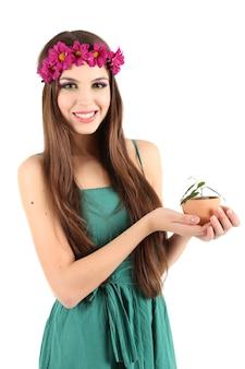 白で隔離の緑の植物と鍋を保持している彼女の頭に装飾的な花輪を持つ若い美しい少女