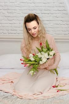 ホテルで長いドレスの花と若い美しい少女