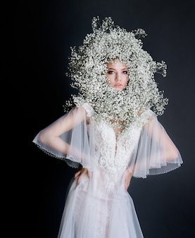 Young beautiful girl with fresh gypsophila wreath on the face dressed in white tender dress on the dark background