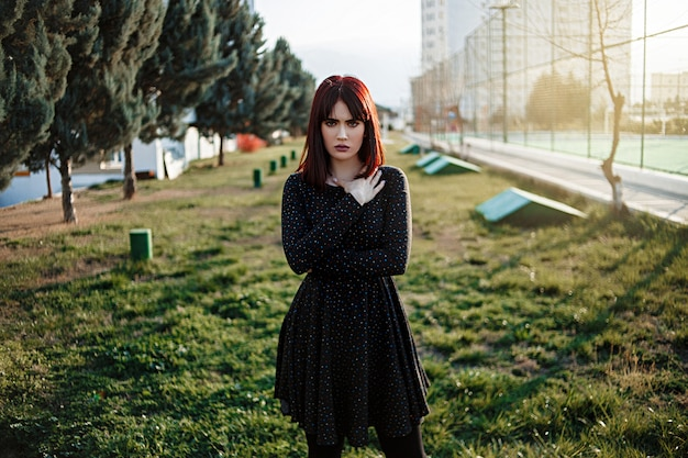 Young beautiful girl with heavy and sullen look in black dress outside posing during sunset