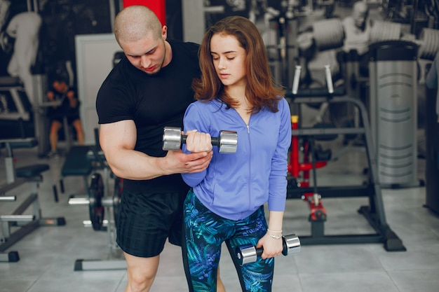 A young and beautiful girl with her boyfriend training in a gym
