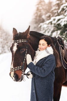 Young beautiful girl with a horse in winter in nature. human-animal friendship