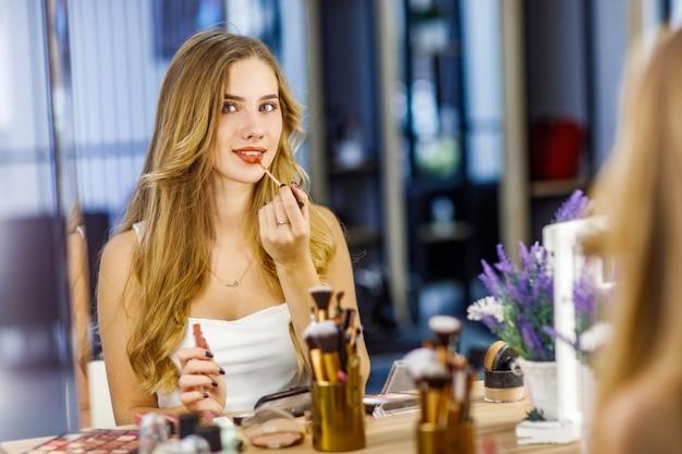 긴 금발 머리를 가진 젊은 아름다운 소녀는 거울 앞에서 빨간 립스틱으로 입술을 그립니다