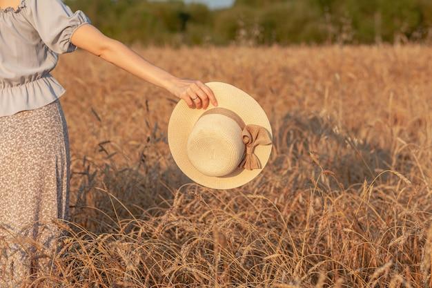 Молодая красивая девушка с длинными вьющимися волосами позирует в пшеничном поле летом на закате. девушка держит шляпу в руке на фоне пшеничного поля. вид со спины. тонировка.