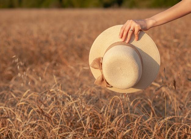 Молодая красивая девушка с длинными вьющимися волосами позирует в пшеничном поле летом на закате. девушка держит шляпу в руке на фоне пшеничного поля. вид со спины. тонировка. Premium Фотографии