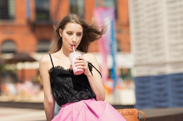 Молодая красивая девушка с длинными волосами пьет фруктовый коктейль.