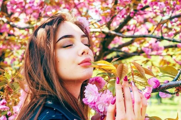 長い髪の美しい少女は、桜の開花の近くで春の自然の美しさを楽しんでいます