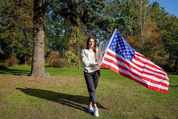 흰 스웨터와 청바지를 입은 긴 머리를 한 아름다운 소녀는 공원에서 화창한 가을날 큰 미국 국기를 들고 웃고 있습니다. 미국 국기와 함께 공원에서 소녀