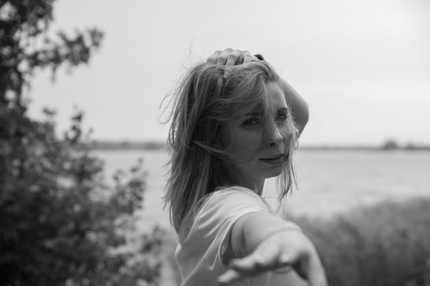 Молодая красивая девушка с длинными волосами в белом халате в солнечный день протягивает руку вперед