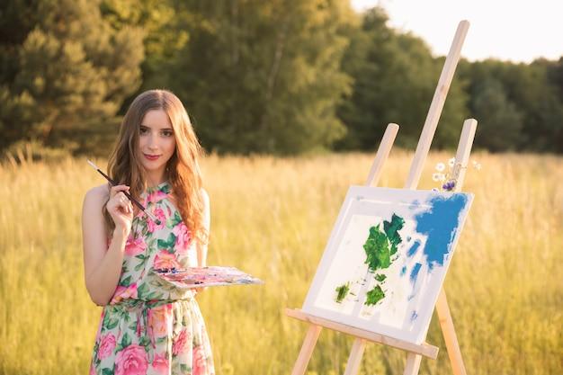 Молодая красивая девушка с длинными натуральными волосами рисует картину в то время как с мольбертом на природе.