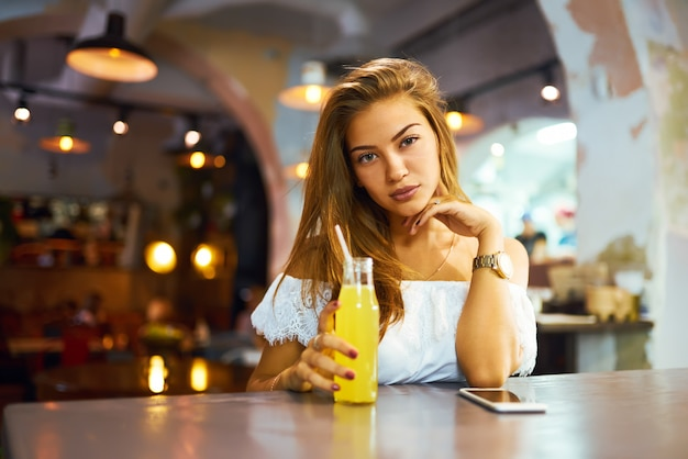 Young, beautiful girl with a lovely smile sitting in a cafe drinking lemonade and using a phone