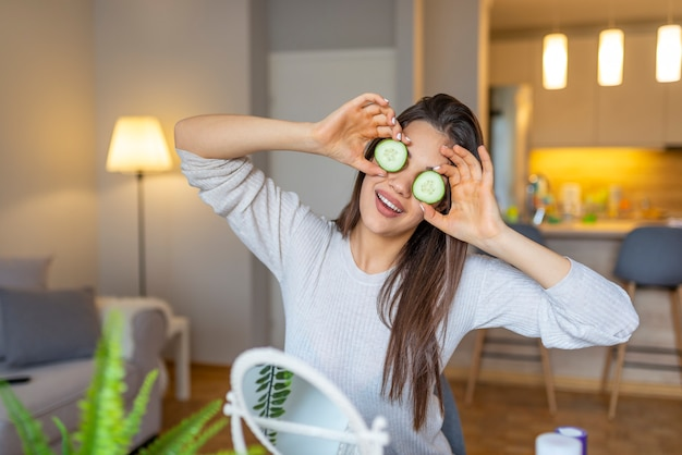 Young beautiful girl with perfect clean skin smiling holding cucumber slices. beauty cosmetology