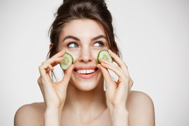 Young beautiful girl with perfect clean skin smiling holding cucumber slices over white background. beauty cosmetology and spa.