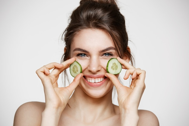 Young beautiful girl with perfect clean skin smiling looking at camera holding cucumber slices over white background. beauty cosmetology and spa.