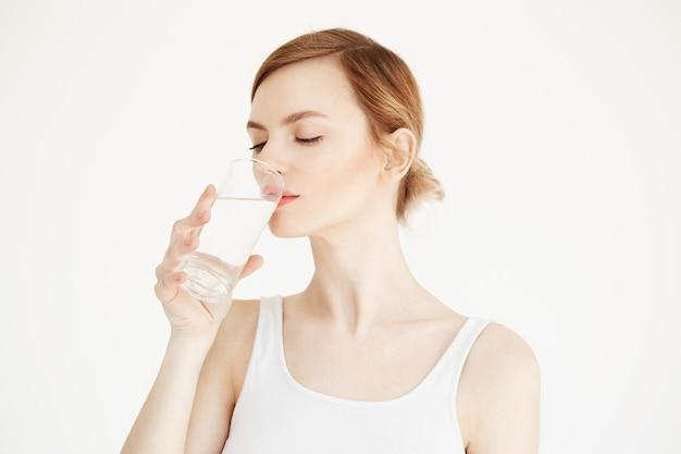 完璧な肌の飲料水を持つ美しい少女。美容と健康のライフスタイル。フェイシャルトリートメント。