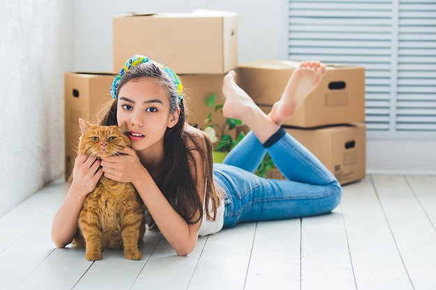 Young beautiful girl with red cat, and with boxes for the move
