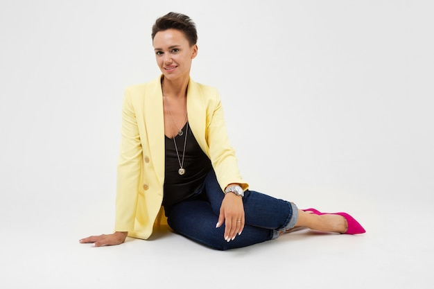 A young beautiful girl with short dark hair, makeup and wristwatch in a yellow jacket, red boat shoes sits on the floor