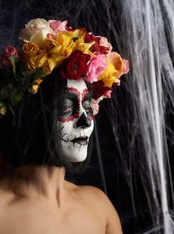 Young beautiful girl with traditional mexican death mask.
