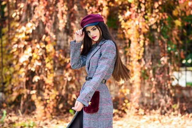 Young beautiful girl with very long hair wearing winter coat and cap in autumn leaves