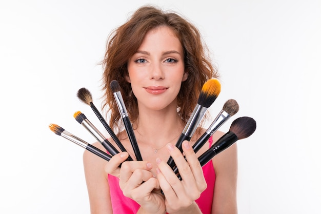 Young beautiful girl with wavy brown hair, clean skin, flat teeth, beautiful smile, in pink jersey, holds a variety of makeup brushes