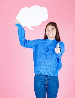 Giovane bella ragazza con una bolla bianca per il testo che mostra un pollice in su.
