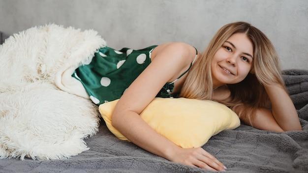Молодая красивая девушка проснулась дома. она лежит на желтой подушке и накрыта белым одеялом. блондинка улыбается