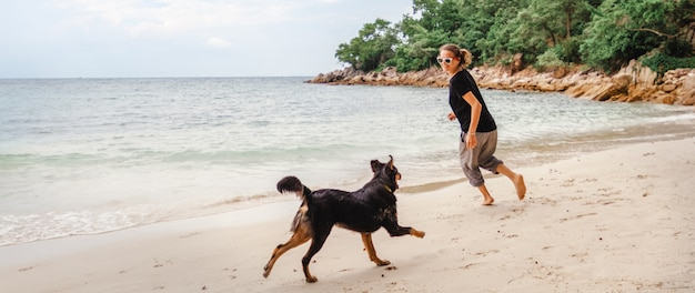 Young beautiful girl woman runs having fun with her dog on the beach barefoot in the sand