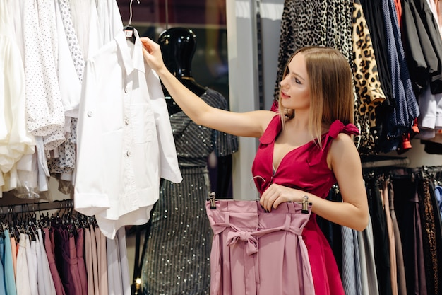 A young beautiful girl in a women's clothing store chooses a white blouse and pink skirt from a new collection.