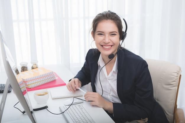Молодая красивая девушка, работающих на ноутбуке в малых средних предприятий. она управляет телефонами и компьютерами